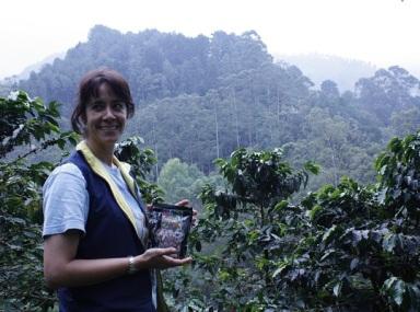 En kvinna står i en kaffeodling och ler. I handen har hon ett kaffepaket