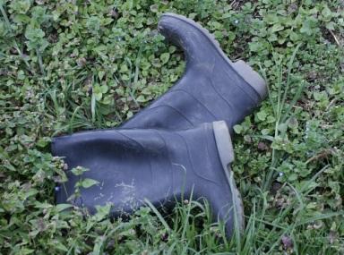 Ett par svarta regnstövlar som ligger på en grässmatta