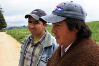 Lázaro står och tittar ut över fälten tillsammans med en granne